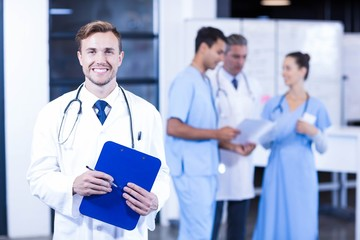 Doctor holding medical report and smiling at camera