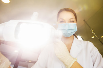 young women dentist with sterile mask readily approaching a patient with dental instruments held in the hands protected with surgical gloves young dentist with sterile mask