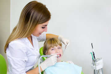Young handsome dentist treats tooth child, a woman dentist