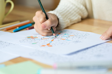 Close-up image of woman drawing geometric figures