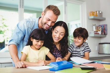 Happy parents assisting children doing homework