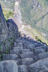 Stone stairs climbing Machu Picchu peak in  Peru