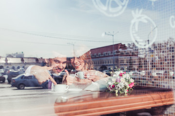 Bride and groom drinking coffee at an outdoor cafe. Reflections
