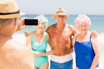 Senior man taking picture of his friends