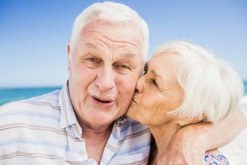 Senior woman kissing senior man