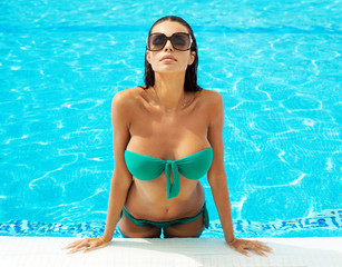 Portrait of sexy model in swimming pool wearing sunglasses