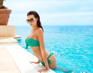 Fashion model in swimming pool wearing bikini and sunglasses