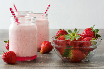 Delicious strawberry smoothie on wood