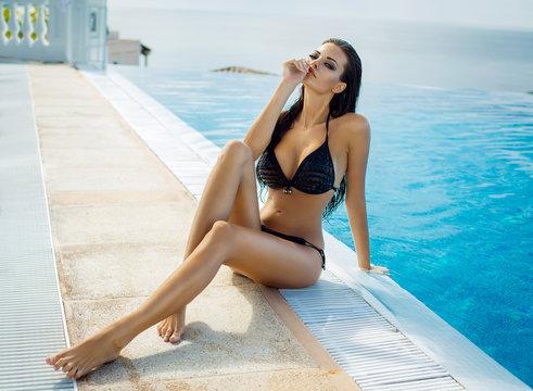 Beautiful woman wearing black bikini by the pool in summer scene