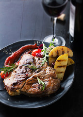 Grilled meat T-Bone with vegetables, spices and glass of wine