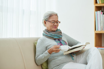 Aged elegant woman drinking coffee when reading a book