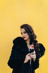Beautiful girl with the phone on a yellow background