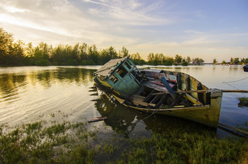 Abandoned fishing boat with beautiful sunset near the river.