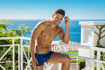 Handsome smiling man wearing swimming trunks in sea scenery