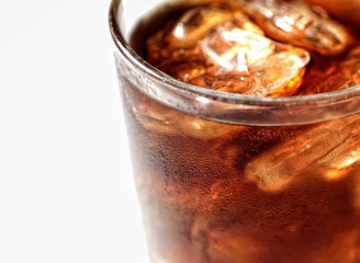Cold cola with ice in a glass on a white background