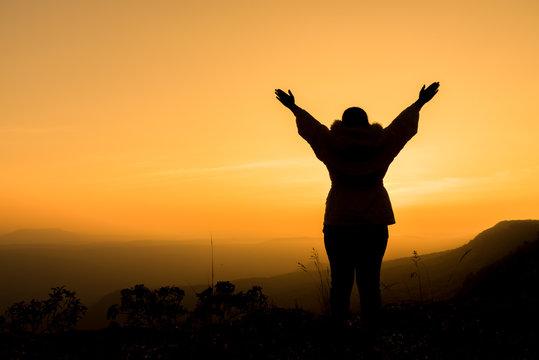 woman raising her arms and enjoying the beautiful sunset