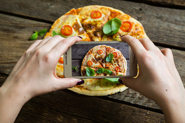 Girl photographs pizza on your smartphone