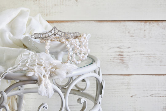 image of white pearls necklace and diamond tiara on vintage table. selective focus