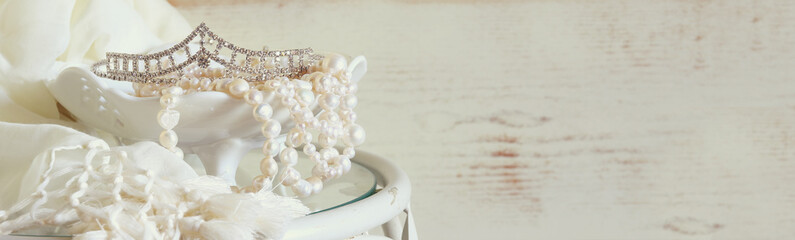 website banner background of white pearls necklace and diamond tiara on vintage table. toned image. selective focus