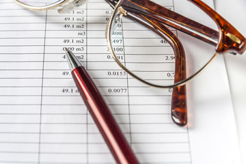 A Pen And Eyeglasses On a Page With Financial Data.