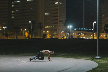 Man working out at night in urban park Fototapete