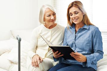 Alte Frau und Tochter schauen Fotoalbum an