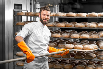 Handsome baker in uniform with orange working gloves putting with shovel from the oven bread loafs on the shelves at the manufacturing