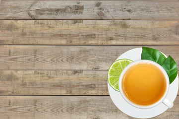 white cup with tea, lime and tea green leaves on wooden table ba