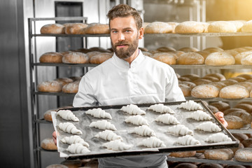 Handsome baker in uniform holding tray full of freshly baked croissants at the manufacturing