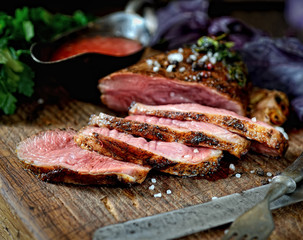 uicy grilled piece of meat on a cutting board, basil, parsley, spices