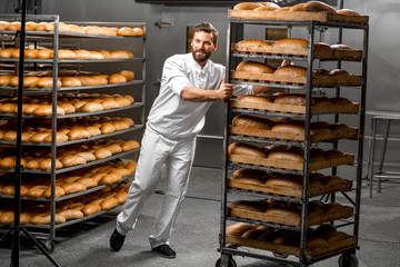 Handsome worker in uniform carrying shelves with bread at the bakery manufacturing