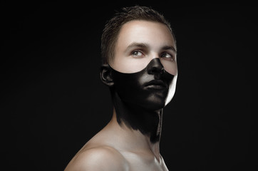 Handsome young guy with make-up with black mask on her face isolated on a dark background in the studio