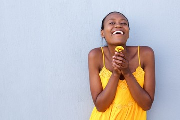 Cheerful young african woman holding a flower