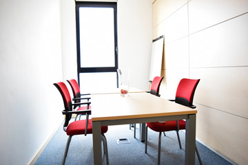 Small light empty office room with table and red chairs