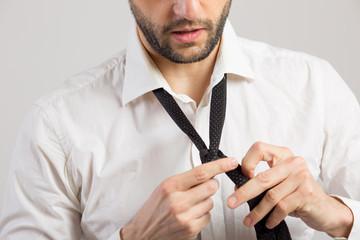 Man ties a necktie knot