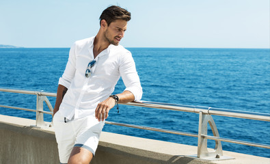 Handsome man wearing white clothes posing in sea scenery