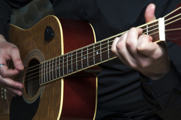 Closeup of man's hands playing on guitar