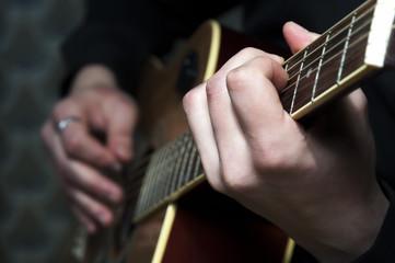 Closeup of acoustic guitar in man's hands.