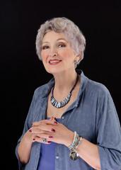 Older woman posing with paua shell stick bar beads