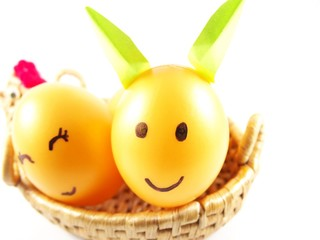 Plastic easter eggs, decorated light green rabbit ears with drawing happy face with smiling in handmade basket