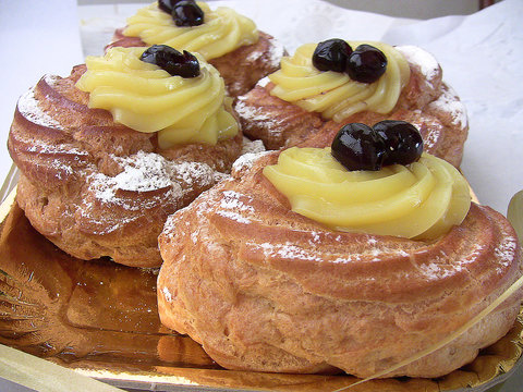 Naples, Italy - March 19, 2016: zeppole of Saint Joseph, Italian pastry  with flour, sugar, eggs, olive oil, custard, decorated with a sour cherry. Father's Day cake.