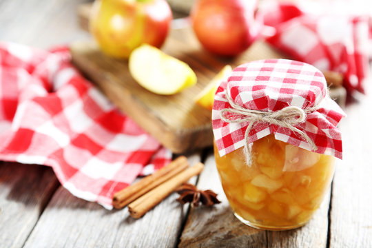 Apple jam in jar on a grey wooden table