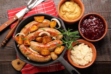 White sausages with potatoes baked in a frying pan