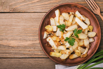 Fried potatoes with parsley and onion in an earthenware dish