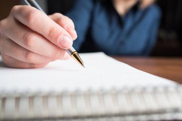 Девушка рисует в пустой тетради ручкой, вид сбоку близко