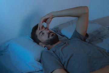 sleep disorder, insomnia. young beard man lying on the bed awake