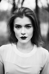 portrait of a beautiful girl in a black coat on the nature