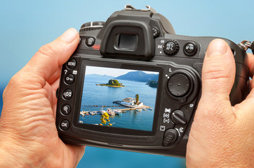 Photo of church and sea on camera display during the summer vacation. Travel photography.