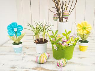Schöne Oster-Tischdekoration mit bemalten Eiern, Frühlingsblumen und selbstgemachte Stoffblumen in Pastellfarben