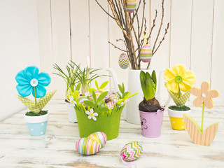 Ostereier, Osterzweig und Frühlingsblumen
